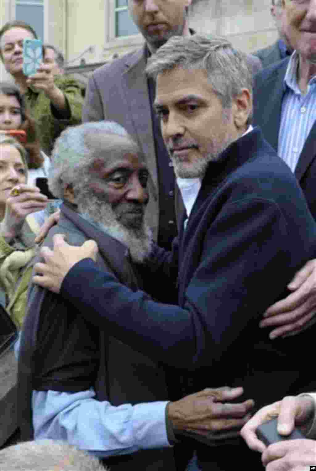 Actor George Clooney embraces activist Dick Gregory during a protest at the Sudan Embassy in Washington, Friday, March 16, 2012. The demonstrators are protesting the escalating humanitarian emergency in Sudan that threatens the lives of 500,000 people. (A