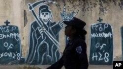Una mujer policia camina frente a un mural pintado por las pandillas, durante un patrullaje en una zona de la capital salvadoreña controlada por las maras.