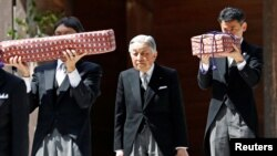 FILE - Japan's Emperor Akihito, flanked by Imperial Household Agency officials carrying two of the so-called Three Sacred Treasures of Japan, leaves the main sanctuary as he visits the Inner shrine of the Ise Jingu shrine, ahead of his abdication, in Ise, Japan, April 18, 2019.