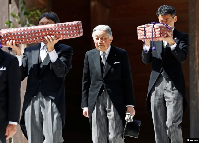 FILE - Japan's Emperor Akihito, flanked by Imperial Household Agency officials carrying two of the so-called Three Sacred Treasures of Japan, leaves the main sanctuary as he visits the Inner shrine of the Ise Jingu shrine, ahead of his April 30, 2019 abdication.