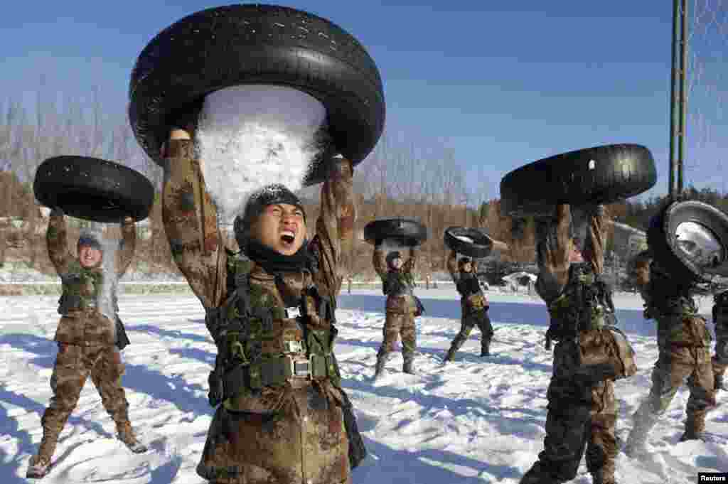 People's Liberation Army (PLA) soldiers pour snow from a tire onto their head during a training session in Heihe, Heilongjiang province, China, Dec. 24, 2014.