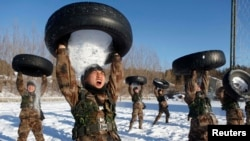 People's Liberation Army (PLA) soldiers pour snow from a tire onto their head during a training session in Heihe, Heilongjiang province, December 24, 2014.