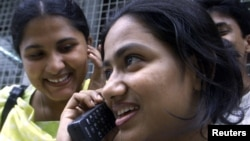 A Bangladeshi student talks on a mobile phone at Dhaka University campus, July 2001.