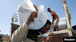 FILE - A man carries a sack of food aid from the WFP, at the Um Rakuba refugee camp in Sudan, where Tigray refugees stay, Dec. 3, 2020.