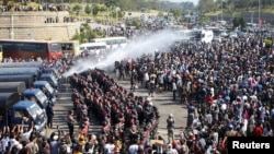 Police fire a water cannon at protesters demonstrating against the coup and demanding the release of elected leader Aung San Suu Kyi, in Naypyitaw, Myanmar, February 8, 2021. (REUTERS)
