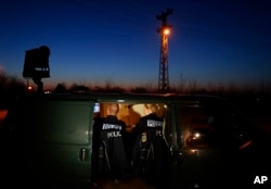 FILE - members of the German border police sit in a van as they check a security camera while monitoring a stretch of the Serbian border with Hungary in the village of Hajdukovo, some 180 kilometers north of Belgrade, Serbia, Feb. 13, 2015.