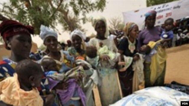 Un grupo de mujeres de Koleram, en el sur de Niger, reciben alimentos para combatir la subnutrición infantil.