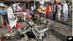 民众2013年5月20日在巴士拉一家热闹的餐馆前注视着汽车炸弹爆炸现场。