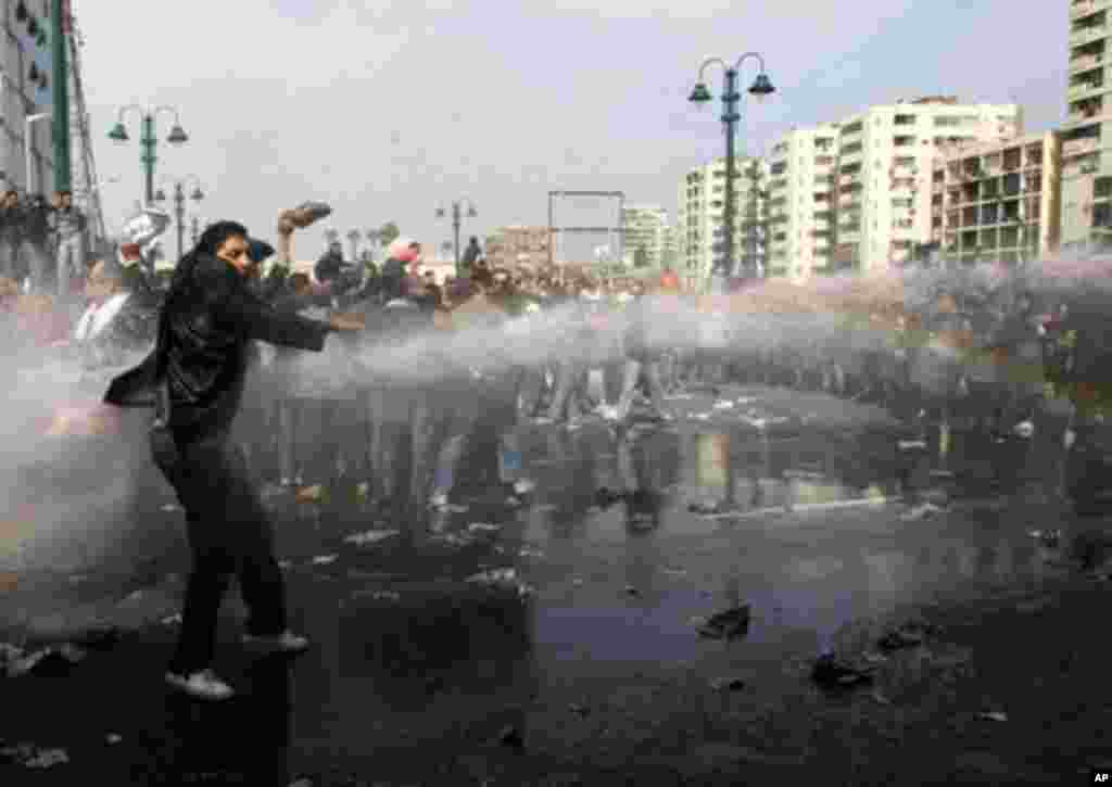 A demonstrator stands in front of police water canons during a protest in Cairo January 28, 2011. Police and demonstrators fought running battles on the streets of Cairo on Friday in a fourth day of unprecedented protests by tens of thousands of Egyptians