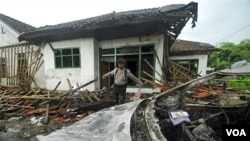 Seorang polisi memeriksa kerusakan di Cikeusik, Banten (7/2). Pelaku kekerasan di Cikeusik, yang menewaskan 3 orang, hanya divonis antara 3-6 bulan penjara.