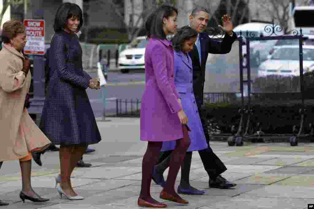 President Barack Obama, accompanied by his daughters Sasha and Malia, first lady Michelle Obama and mother-in-law Marian Robinson, waves as they arrive at St. John's Church in Washington, Monday, Jan. 21, 2013