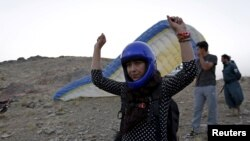 Afghan paraglider Leeda Ozori, 21, prepares to practice, outside Kabul, September 17, 2015.