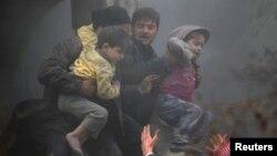 Warga di Damaskus membawa anak-anak yang terluka dalam serangan udara oleh pasukan pemerintah di distrik Duma (7/1).