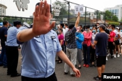 A police officer gestures at a photographer as people line up to get a nucleic acid test at a sport center after a spike of cases of the coronavirus disease (COVID-19), in Beijing, China June 17, 2020. REUTERS/Thomas Peter