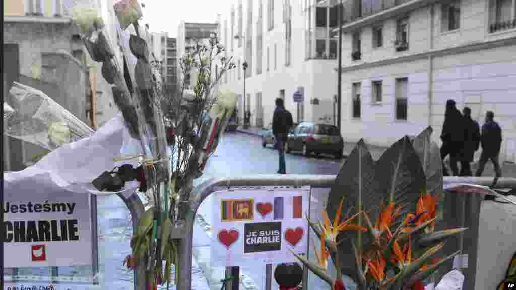 Des fleurs sont attachées à la clôture de sécurité devant le siège de Charlie Hebdo une semaine après l'attaque sur le journal, Paris, France, le 14 janvier 2015.