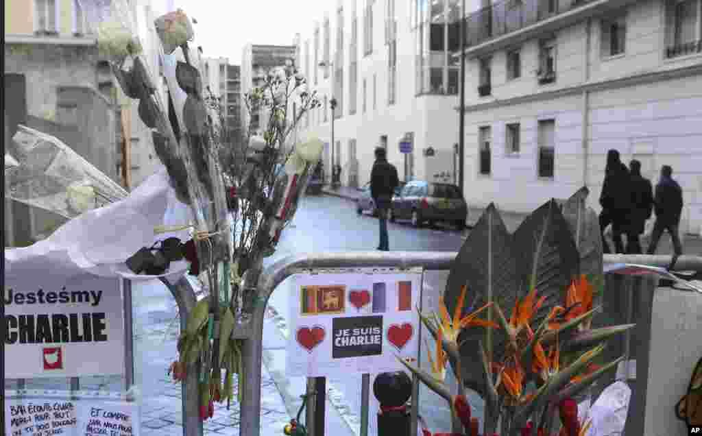 Karangan bunga di pagar pengaman di luar kantor pusatCharlie Hebdo seminggu setelah serangan terhadap tabloid itu, di Paris, Perancis (14/1). (AP/Jacques Brinon)