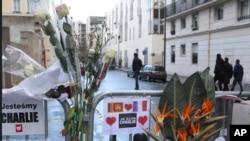 Bunga-bunga dipasang di pagar di luar kantor pusat Charlie Hebdo di Paris, seminggu setelah serangan terhadap tabloid tersebut. (Foto: Dok)