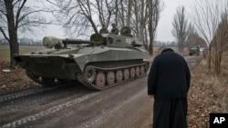 Seorang pendeta memberi hormat kepada para pejuang separatis pro-Rusia berkendaraan lapis baja di Yelenovka, dekat Donetsk, Ukraine (27/2)