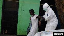 Seorang petugas kesehatan dengan pakaian pelindung membawa seorang pasien Ebola perempuan ke mobil ambulans di Monrovia, Liberia (15/9).
