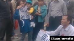 王登朝妻子怀抱尚未见过父亲的幼子与声援者在二审法庭外。(网络图片)