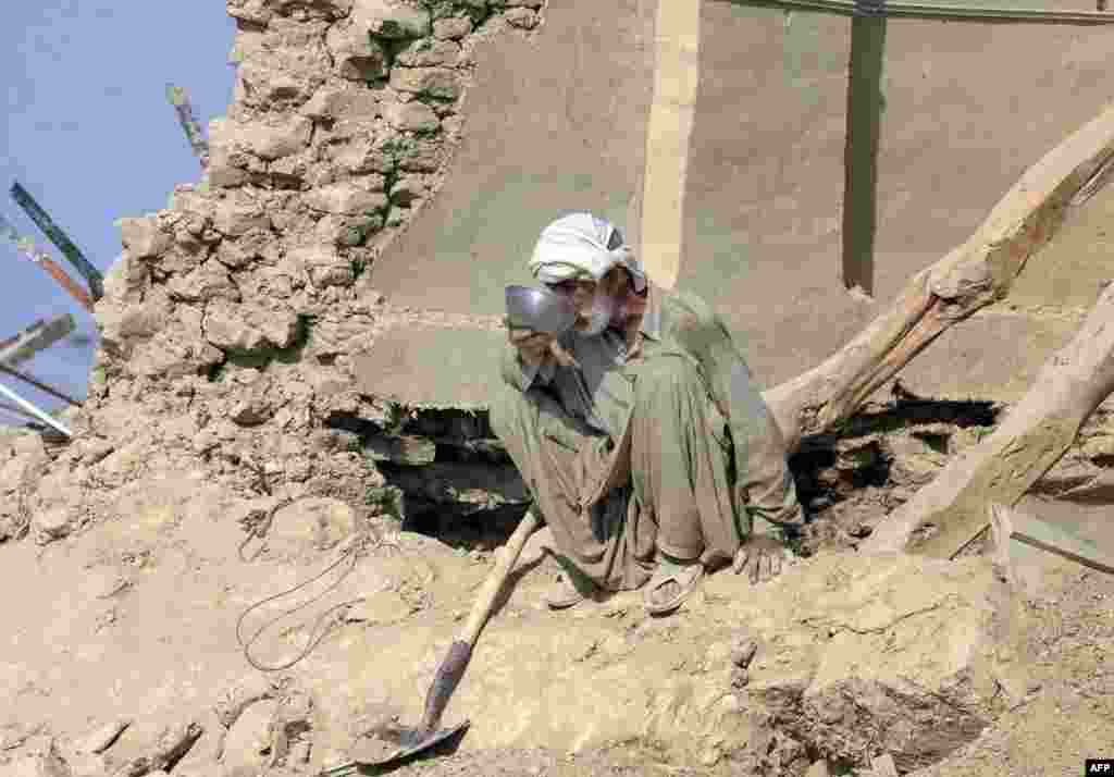 A Pakistani earthquake survivor drinks water at his collapsed mud house in the Dhall Bedi Peerander area of the earthquake-devastated district of Awaran. Tens of thousands of survivors of earthquake waited for help in soaring temperatures as the death toll rose to nearly 350.