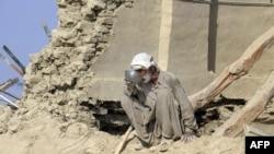 지난 24일 발생한 지진 생존자가 붕괴된 자택에서 물을 마시고 있다.