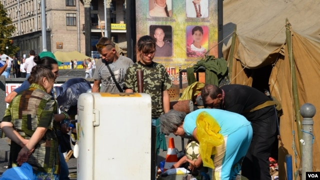 Protesters reclaim their belongings, including a battered fridge, Independence Square, Kyiv, Ukraine, Aug. 11, 2014. (Jamie Dettmer/VOA)
