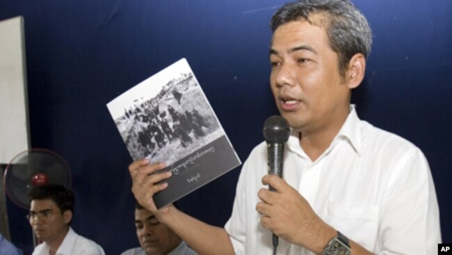 Youk Chhang, a leading Cambodian genocide researcher, shows a copy of the Cambodian version of a Khmer Rouge history textbook to teachers in Takeo province, July 3, 2012.