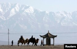 FILE - Visitors ride camels outside the Jiayuguan Pass Town in front of the snow-covered Qilian Mountains in Jiayuguan, northwest China's Gansu province April 28, 2007. REUTERS/Jason Lee