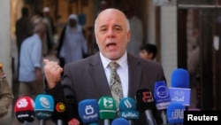 FILE - Iraqi Prime Minister Haider al-Abadi speaks to reporters in the Shi'ite holy city of Najaf, south of Baghdad, Oct. 20, 2014.
