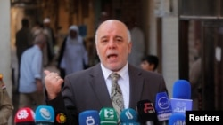 FILE - Iraqi Prime Minister Haider al-Abadi speaks to reporters in the Shi'ite holy city of Najaf, south of Baghdad.