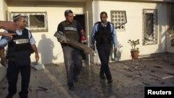 Сотрудник полиции Израиля держит в руках остатки ракеты, выпущенной с территории Сектора Газа. Офаким, Израиль. 18 ноября 2012 года