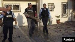 Một chuyên viên về chất nổ của cảnh sát Israel cầm mảnh vỡ của tên lửa bắn từ Dải Gaza vào thị trấn Ofakim, miền nam Israel, 18/11/12