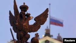 A sculpture of a double-headed eagle, a national symbol of Russia, is seen in front of a Russian national flag flying at half-mast on the roof of the State Hermitage Museum in St. Petersburg.