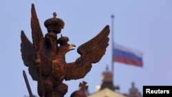 FILE - A sculpture of a double-headed eagle, a national symbol of Russia, is seen in front of a Russian national flag flying at half-mast on the roof of the State Hermitage Museum in St. Petersburg.