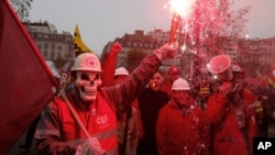 Thành viên công đoàn, cầm pháo sáng, biểu tình trước lối vào phòng trưng bày xe hơi trong thủ đô Paris, 9/10/12