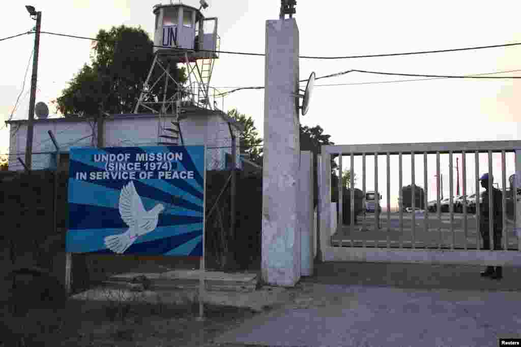 A U.N. peacekeeper stands at the entrance of a U.N. base next to the Quneitra border crossing between the Israeli-controlled Golan Heights and Syria, Aug. 29, 2014.