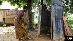 Une femme nettoie ses toilettes dans le quartier de Kindele à Kinshasa le 17 novembre 2017.