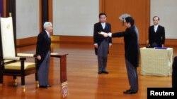 PM baru Jeoang, Shinzo Abe (dua dari kanan) menerima sebuah sertifikat dari Kaisar Akihito (kiri), diawasi oleh mantan PM Yoshihiko Noda (dua dari kiri) dalam upacara pelantikan PM Jepang di Istana Kekaisaran Jepang di Tokyo (26/12).