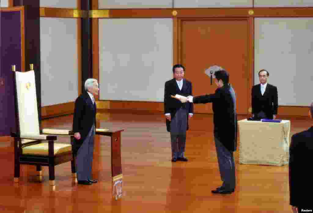 Japan's new Prime Minister Shinzo Abe (2nd R) receives a certificate from Emperor Akihito (L) as former Prime Minister Yoshihiko Noda (2nd L) watches, during a ceremony at the Imperial Palace in Tokyo, December 26, 2012.