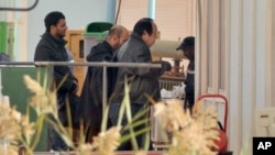 An unidentified person is followed by Algerian officials as they enter a morgue holding the bodies of the persons killed during the hostage situation at the gas plant, in Ain Amenas, Algeria, January 21, 2013. (AP)