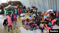 Families displaced by recent fighting in South Sudan, camp in a warehouse inside the United Nations Mission in Sudan facility in Jabel, on the outskirts of capital Juba, Dec. 23, 2013.