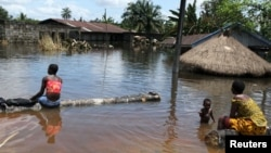 People sit in front of a submerged building in the Patani community in Nigeria's Delta state, which was recently hit by severe floods, October 15, 2012.