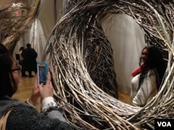 Jessica Liou takes a picture of fellow museum visitor Megan Limson at the WONDER exhibit, Renwick Gallery, Washington. (J. Taboh/VOA)