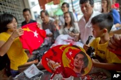 FILE - People gather to buy merchandise with pictures of Myanmar opposition leader Aung San Suu Kyi at a shop run by her National League of Democracy party in Yangon, Myanmar, Nov. 10, 2015.