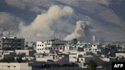 Asap mengepul pasca serangan udara pasukan Suriah terhadap Hamouria, Ghouta timur di pinggiran Damaskus (3/3).