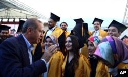 FILE - Turkey's President Recep Tayyip Erdogan speaks with students at the Sabahattin Zaim University in Istanbul, June 5, 2016.