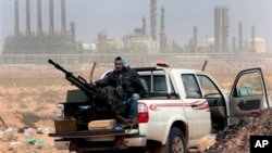In this March 5, 2011 file photo, an anti-government rebel sits with an anti-aircraft weapon in front an oil refinery, after the capture of the oil town of Ras Lanouf, eastern Libya. The official Libyan news agency said Sunday, April 6, 2014 that the country's main militia in the east has agreed to hand back control of four oil terminals it captured and shut down last summer in its demand for a share in oil revenues. The shutdown has cost Libya millions of dollars. (AP Photo/Hussein Malla, File)