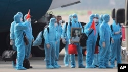 Vietnamese COVID-19 patients in protective gear, holding Vietnamese flags and carrying a portrait of the national leader Ho Chi Minh, arrive at the Noi Bai airport in Hanoi, Vietnam, on Wednesday, July 29, 2020. (Tran Huy Hung/VNA via AP)