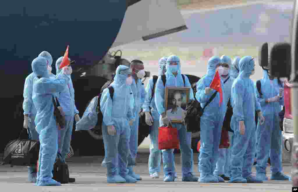 Vietnamese COVID-19 patients in protective gear hold Vietnamese flags and carry a portrait of the national leader Ho Chi Minh as they arrive at the Noi Bai airport in Hanoi. A total of 129 patients who were working in Equatorial Guinea were brought home in a repatriation flight.